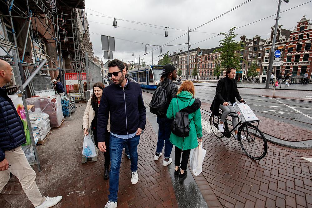 Een man op de fiets en voetgangers passeren een bouwplaats aan het Rokin in Amsterdam.<br /> <br /> Pedestrians and a cyclist pass a construction area at the Rokin in Amsterdam.