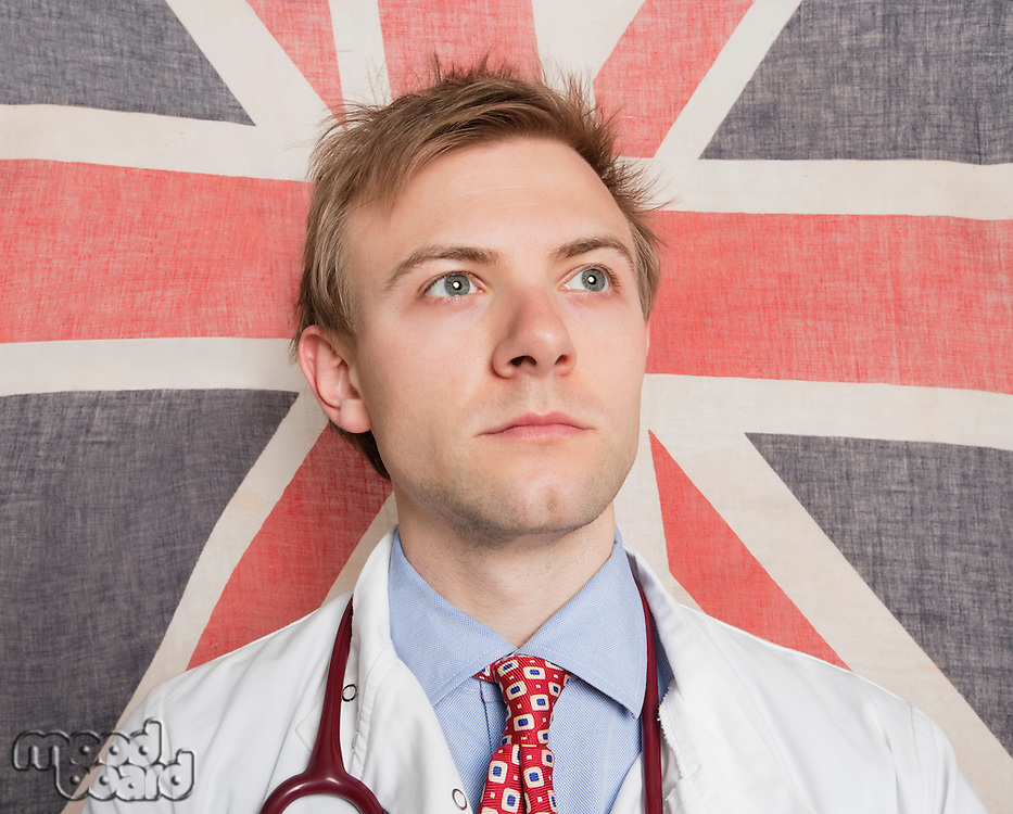 Caucasian doctor looking away with British Flag in background