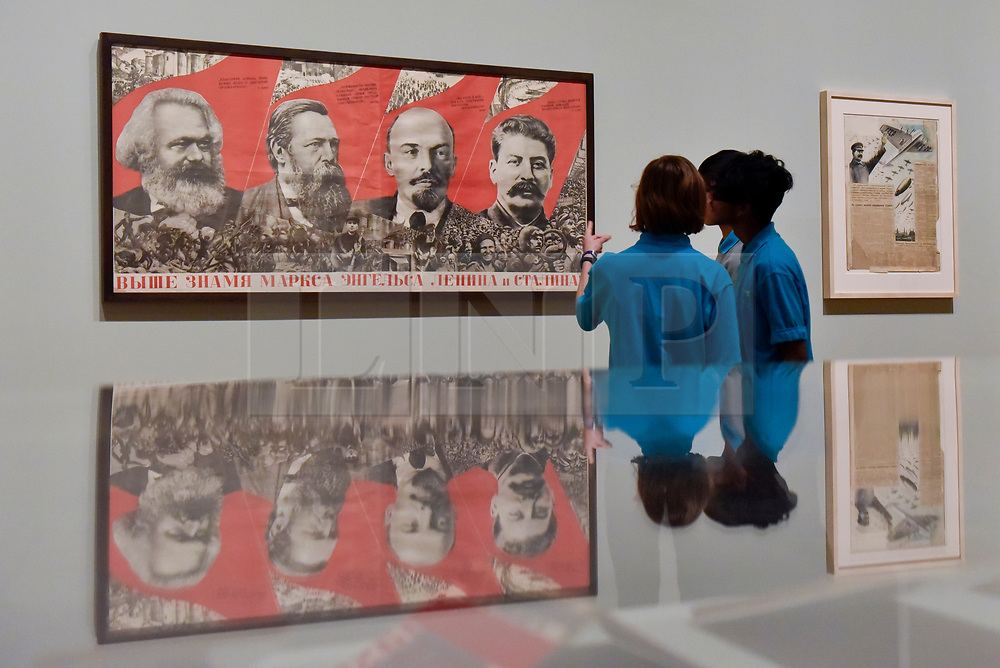 """© Licensed to London News Pictures. 07/11/2017. London, UK.  Students from Thomas Tallis School, Kidbrooke, south London, look at """"Under the Banner of Marx, Engels, Lenin and Stalin!"""", 1933, by Gustav Klutsis, at a preview of """"Red Star Over Russia: A Revolution in Visual Culture 1905-55"""" at Tate Modern.  The exhibition marks the centenary of the October Revolution and presents the visual history of Russia and the Soviet Union with works drawn from the late graphic designer David King. Photo credit: Stephen Chung/LNP"""