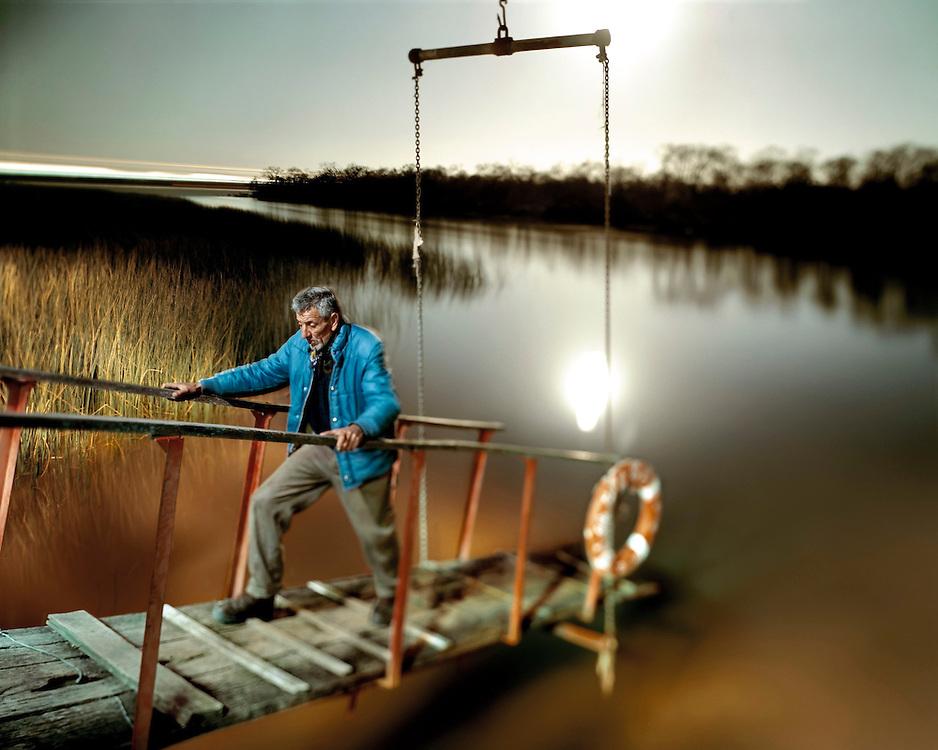 """Sergio camina sobre el puente del """"Nimersat"""", un barco draga abandonado donde vive, a orillas del Río Capitán."""