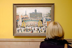 Visitor looking at painting VE Day by LS Lowry  on display at Kelvingrove Art Gallery and Museum in Glasgow United Kingdom