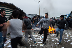 October 24, 2016 - Calais, France - Migrants from Afghanistan dance in the Calais Jungle on the main road. After registration, the migrants are distributed on buses. The refugee camp on the coast to the English Channel is to be cleared today. The approximately 8,000 refugees are distributed after the registration by busses to various reception centers in France, on October 24, 2016. (Credit Image: © Markus Heine/NurPhoto via ZUMA Press)