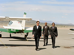 three men in suits walking at a small airport in Santa Fe, New Mexico