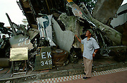 Army Museum. Former North Vietnamese soldier posing with pieces of a shot down American B-52 bomber.