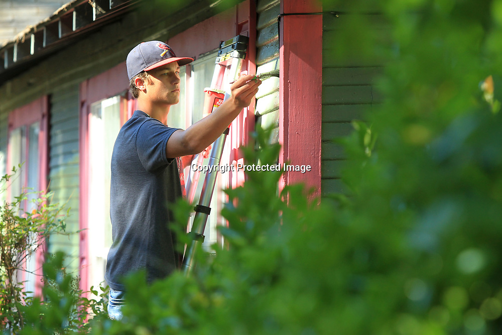 Nathan Dothsuk, 17, from Cadiz Kentucky, and a member of the Crossroads Fellowship Church, works with World Changers to paint the house of Tupelo resident Robi Gutierrez on Chestnut Street Wednesday morning.