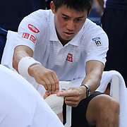 Kei Nishikori, Japan, receives treatment to his toes during his five set win over Stan Wawrinka, Switzerland, in the Men's Singles Quarterfinals during the US Open Tennis Tournament, Flushing, New York, USA. 3rd September 2014. Photo Tim Clayton