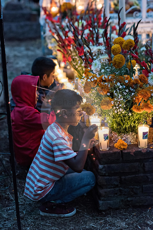 Young children help light candles at the decorated gravesite of two brothers killed on the same day for the Day of the Dead festival October 31, 2017 in Tzintzuntzan, Michoacan, Mexico.