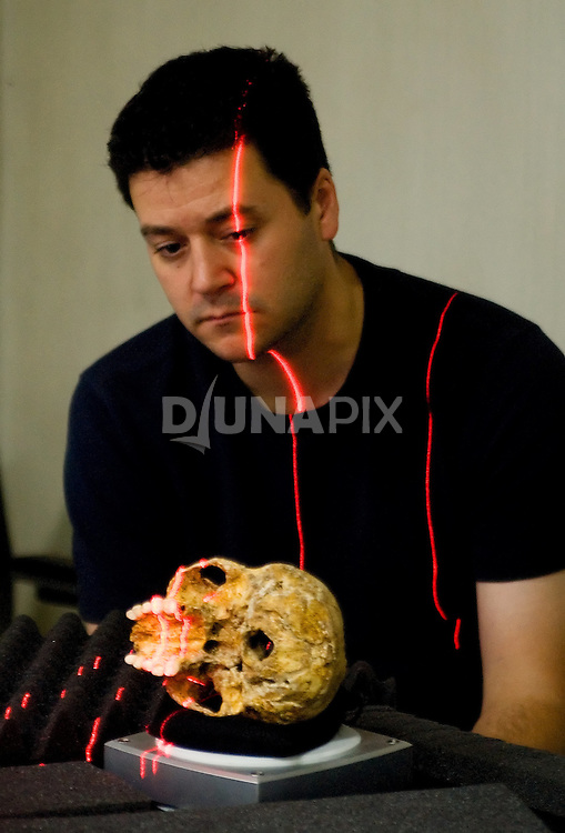 Dr. Matthew Tocheri contemplates the tiny cranium of Homo floresiensis while producing a detailed 3D scan.