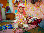 "04 APRIL 2015 - CHIANG MAI, CHIANG MAI, THAILAND:  A Tai boy sits in an alter in his family's living space at Wat Pa Pao during the Poi Sang Long Festival. Friends and family will visit him and pray with him before the ordination ceremony. The Poi Sang Long Festival (also called Poy Sang Long) is an ordination ceremony for Tai (also and commonly called Shan, though they prefer Tai) boys in the Shan State of Myanmar (Burma) and in Shan communities in western Thailand. Most Tai boys go into the monastery as novice monks at some point between the ages of seven and fourteen. This year seven boys were ordained at the Poi Sang Long ceremony at Wat Pa Pao in Chiang Mai. Poy Song Long is Tai (Shan) for ""Festival of the Jewel (or Crystal) Sons.     PHOTO BY JACK KURTZ"