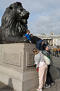 A tourist is pushed up on to the plinth of one of four lions in Trafalgar Square, on 8th October 2018, in London, England. The lions are by Sir Edwin Henry Landseer RA, an English painter well known for his paintings of animals—particularly horses, dogs and stags. The best known of Landseer's works, however, are these lions in Trafalgar Square.