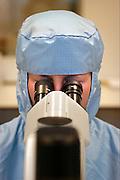 Nederland, Nijmegen, 14-12-2005Een onderzoeker kijkt in een microscoop. Zij  isin een clean room en werkt aan een medicijn tegen kanker.