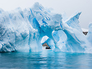 "A Zodiac boat explores a blue iceberg arch melting in Neko Harbor (an inlet of the Southern Ocean), at Graham Land, the north portion of the Antarctic Peninsula, Antarctica. Scientists have measured temperatures on the Antarctic Peninsula as warming faster than anywhere else on earth. An overwhelming consensus of world scientists agree that global warming is indeed happening and humans are contributing to it through emission of heat-trapping ""greenhouse gases,"" primarily carbon dioxide (see www.ucsusa.org). Since the industrial revolution began, humans have increased atmospheric CO2 concentration by 35% (through burning of fossil fuels, deforesting land, and grazing livestock). Published in ""Light Travel: Photography on the Go"" book by Tom Dempsey 2009, 2010."