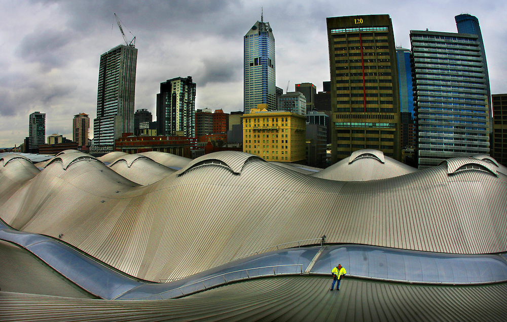 The roof of the newly renamed and renovated Southern Cross Station in Melbourne, Victoria in 2007. A workman is dwarfed on the &quot;wave&quot; roof with the skyline of buildings and offices of the Melbourne CBD in the background..THE AGE Picture by CRAIG SILLITOE ..Century of Pictures, Spencer Street Station, railway station, rail station, silver, domes, city, building, sky..Making of a new Melbourne Exhibition melbourne photographers, commercial photographers, industrial photographers, corporate photographer, architectural photographers, This photograph can be used for non commercial uses with attribution. Credit: Craig Sillitoe Photography / http://www.csillitoe.com<br />