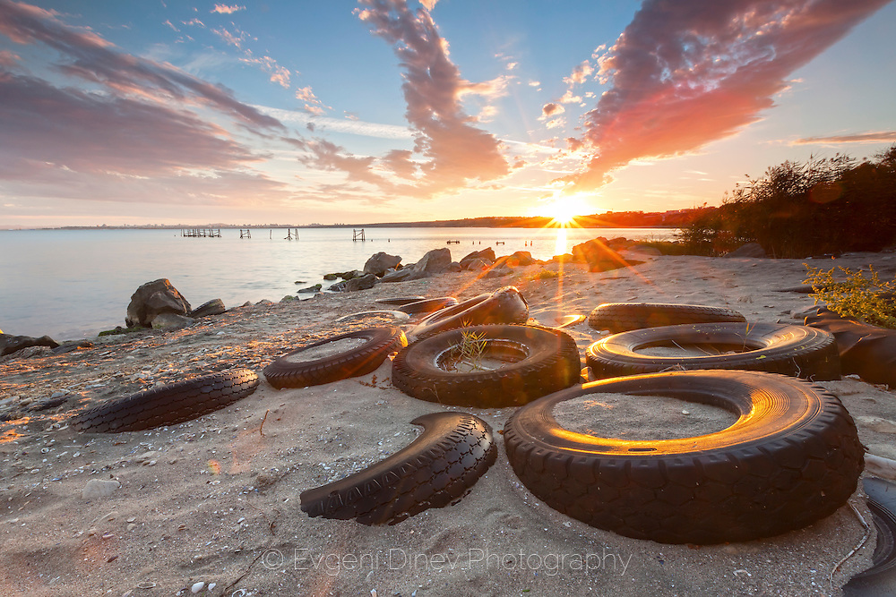 Truck tyres on the beach at sunset