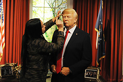 Gemma Sim applies hairspray to a wax figure of Donald Trump in the Oval office, as it is unveiled at Madame Tussauds in London, ahead of his inauguration as the 45th US president.