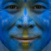 Head and shoulders portrait of male with his face painted blue.
