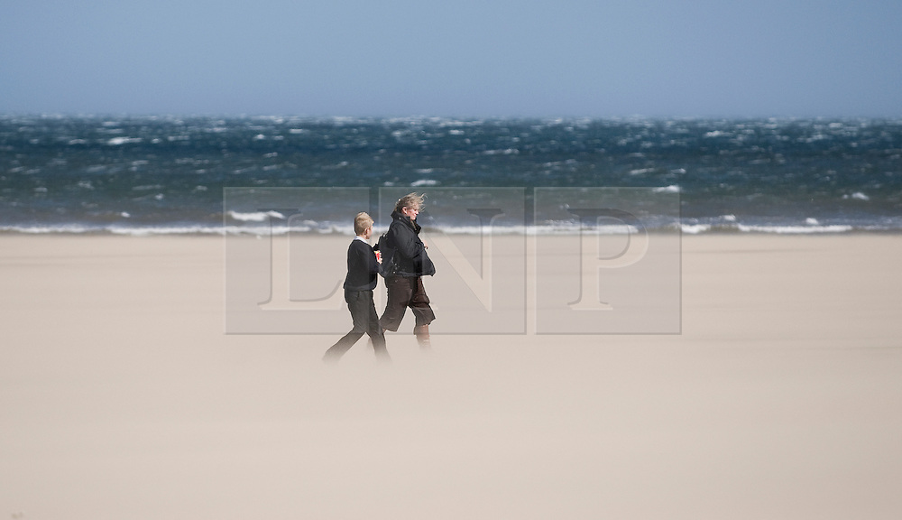 © Licensed to London News Pictures. 12/09/2011..Saltburn Beach, Saltburn, Cleveland, England...A family walk through blowing sands as strong winds blow across the beach at Saltburn in Cleveland...Photo credit : Ian Forsyth/LNP
