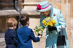 Windsor, UK. 21st April 2019. The Queen is presented with a traditional posy of flowers by local schoolchildren as she leaves St George's Chapel in Windsor Castle with the Dean of Windsor, the Rt Revd David Conner KCVO, after attending the Easter Sunday service.