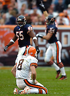 MORNING JOURNAL/DAVID RICHARD.Clevleand quarterback Trent Dilfer rests on his knees as the Chicago Bears defense celebrates downfield after a Dilfer pass was intercepted and returned 72 yards yesterday in the second quarter.