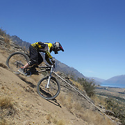 Carl Edmondson from Whakatane in action during the New Zealand South Island Downhill Cup Mountain Bike series held on The Remarkables face with a stunning backdrop of the Wakatipu Basin. 150 riders took part in the two day event. Queenstown, Otago, New Zealand. 9th January 2012. Photo Tim Clayton