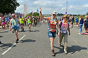 Nederland, Nijmegen, 22-7-2015 Deelnemers aan de 4daagse, vierdaagse, lopen op de tweede dag, de dag van Wijchen, over de voerweg naar de finish op de wedren. Het laatste stuk van het parcours loopt over de Waalkade en door de stad, de Hertogstraat, waar ook de zomerfeesten plaatsvinden. Traditioneel de roze woensdag met als gangmaker entertainer Bennie Solo. The International Four Day Marches Nijmegen is the largest marching event in the world. It is organized every year in Nijmegen mid-July as a means of promoting sport and exercise. Participants walk 30, 40 or 50 kilometers daily, and receive a medal, Vierdaagsekruisje. The maximum paticipants is 45,000 . Foto: Flip Franssen/Hollandse Hoogte