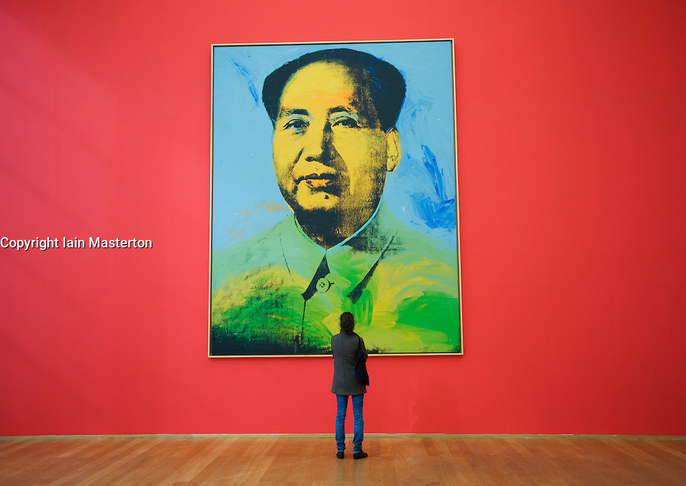 Visitor looking at portrait of Chairman Mao by Any Warhol at Hamburger Bahnhof modern art gallery in Berlin