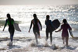 © Licensed to London News Pictures. 10/10/2018. West Wittering, UK. Teenage surfers splash into the sea at West Wittering as unseasonably high temperatures hit parts of the UK. Photo credit: Peter Macdiarmid/LNP