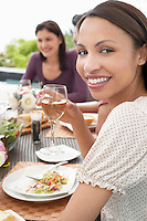 Young Woman Drinking Wine outdoors at a dinner party