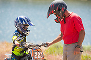Close up of father helping his son with his dirt bike during a family ATV ride on Trapper Creek Road with the Lower Goose Creek Reservoir behind, Oakley, Idaho.
