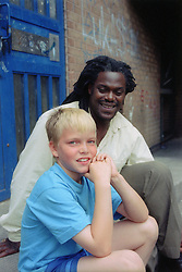 Boy and carer sitting on step outside entrance to block of flats,