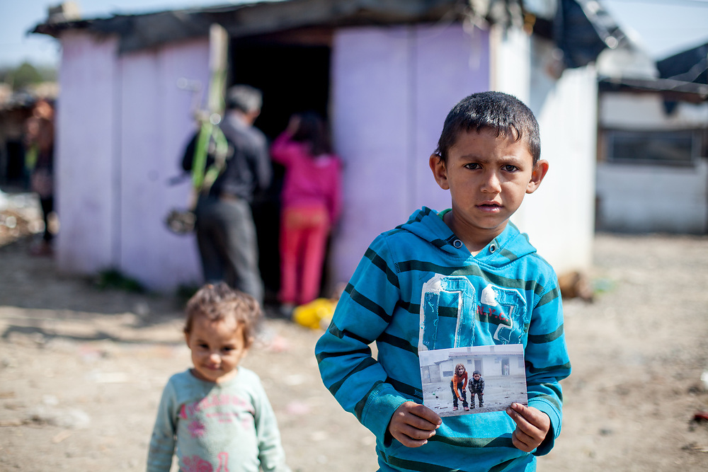 "A boy living at the Roma settlement ""Budulovska Street"" is holding a photograph of himself made two years before. The city of Moldava nad Bodvou has roughly 11200 inhabitants, about 1980 (18%) of them have Roma ethnicity and around 800 are living at the segregated settlement 'Budulovska Street' (2014)."