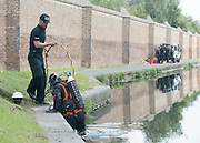 © Licensed to London News Pictures. 09/09/2014. Hanwell, UK. Police divers enter the water.  Police continue to cordon off a section of the Grand Union Canal in Isleworth in the search for missing school girl Alice Gross today 9th September 2014.  Alice Gross of Hanwell, west London, was last seen by her family at about 13:00 BST on 28 August. CCTV footage shows her walking along the Grand Union Canal tow path near the Holiday Inn at Brentford Lock between 13:30 BST and 17:30 BST.. Photo credit : Stephen Simpson/LNP