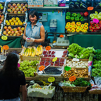 A woman talks to a customer in a food stall in the Mercado Coperto (indoor market) in Trieste, Italy.