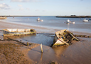 Abandoned old wooden boats rotting on the shoreline on the River Ore at Orford, Suffolk, England