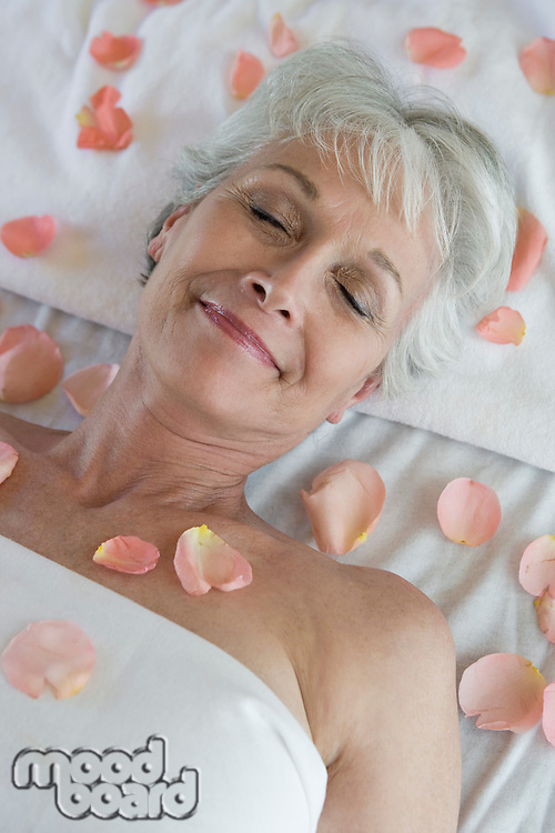 Senior woman covered in petals on bed