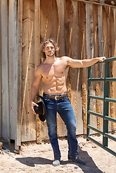 sexy shirtless muscular cowboy by a rustic barn