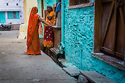 Two neighbour women talk to each other in the morning, in Bundi. The orange of their clothing  contrasts with the blue of the house.