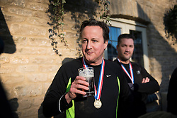 © Licensed to London News Pictures. Prime Minister DAVID CAMERON enjoying  pint of Doom Bar ale after the race. British Prime Minister DAVID CAMERON taking part in The Great Brook Run in Chadlington, Oxfordshire on December 29, 2014. The cross-country course, which is over a mile long, takes competitors through muddy fields, through cold water and under 3-foot wide tunnel. Photo credit : Ben Cawthra/LNP