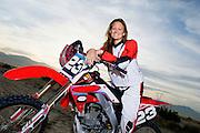 Female motocross racer on bike in desert (portrait)