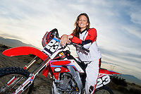Female motocross racer on bike in desert (portrait)