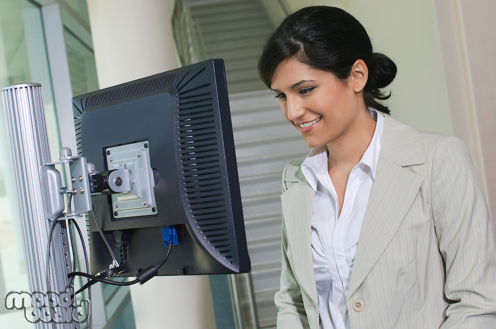 Business woman using computer in office hallway