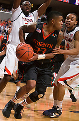 Miami (FL) guard Jack McClinton (33) is defended by Virginia guard Calvin Baker (4) and Virginia center Tunji Soroye (21).  The Virginia Cavaliers fell to the Miami Hurricanes 62-55 at the John Paul Jones Arena on the Grounds of the University of Virginia in Charlottesville, VA on February 26, 2009.