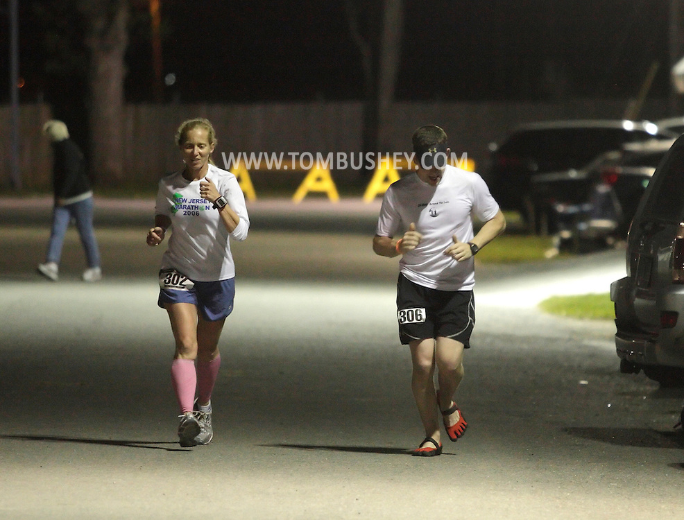 Augusta, New Jersey - Aubrey Blanda, left, and Pete Johnson, run laps around the Sussex County Fairgrounds during the 3 Days at the Fair races on Saturday, May 15, 2010. Both runners were competing in the 12-hour race.