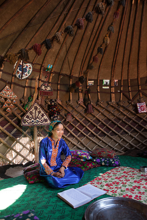 A young women, also a poet, reads from her poetry journal in the family yurt in the desert village of Damla, Turkmenistan