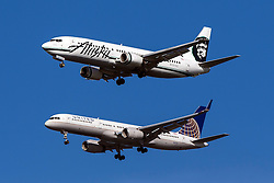 Alaska Airlines Boeing 737-490 (registration N767AS) flies next to United Airlines Boeing 757-224 (registration N41135) on approach to San Francisco International Airport (SFO) over San Mateo, California, United States of America