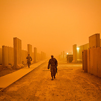 A US soldier passes by blast walls protecting the soldiers living quarters during a sandstorm at the Balad airbase 40 miles north of Baghdad Iraq. March 2011.