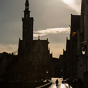A lone cyclist is silhouetted on a cobblestone street running next to a canal in Bruges, Belgium.