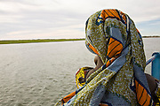 Korioume, Mali 2009 - A young girl from Mali, wrapped head to toe in traditional  colorful wax resist prints, watches the Niger River slide by from the ferry headed south from Timbuktu. The ferry forms the  primary road link to Timbuktu.