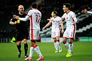 MK Dons Scott Golbourne (12) and team mates remonstrate with the ref after a yellow card during  the EFL Sky Bet League 1 match between Milton Keynes Dons and Peterborough United at stadium:mk, Milton Keynes, England on 30 December 2017. Photo by Nigel Cole.