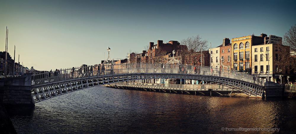 A panorama of the famous Ha'penny Bridge on the river Liffey in Dublin City, Ireland as the sun sets on a clear and sunny day.